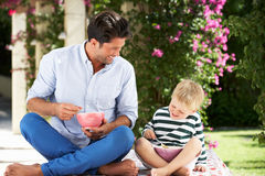 Father And Son Enjoying Breakfast Cereal Outdoors Stock Images