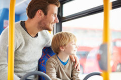 Father And Son Enjoying Bus Journey Together. Looking Out Window Smiling Stock Photo
