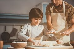 Child learning kneading process with help of dad. Father and son enjoying cooking together. Boy rolling out dough while men controlling operation Stock Photos
