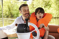 Father And Son Enjoying Day Out In Boat On River Together Royalty Free Stock Photo
