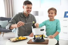Father and son enjoying fondue dinner stock images