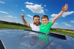 Father and son enjoying freedom on sunroof of car Stock Photos