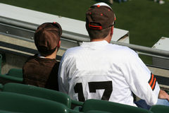 Father & Son enjoying the game. Sitting in stands watching football Royalty Free Stock Image