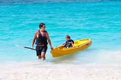 Father and son enjoying kayak ride on troical beach Royalty Free Stock Images