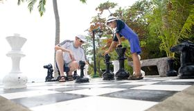 Father and son enjoying lifesize chess game royalty free stock images