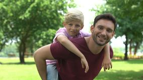 Father and son enjoying piggyback ride, showing thumbs up, support and trust