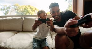 Father and son enjoying playing video game. Portrait of father and son enjoying playing video game in living room. Smiling young men and little boy playing video Stock Images