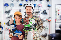 Father and son enjoying purchased roller-skates Stock Images