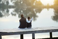Father and son enjoying the sunset on the lake stock images