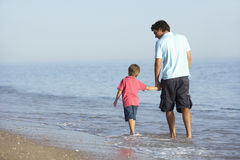 Father And Son Enjoying Walk Along Beach Royalty Free Stock Photo