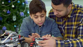 Father and son examine toy tracked ATV stock video footage