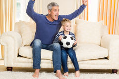Father and son exulting on the sofa Royalty Free Stock Image