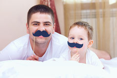 Father and son with false mustaches, playing at home stock photo