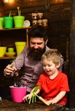 Father and son. Family day. Greenhouse. bearded man and little boy child love nature. happy gardeners with spring. Flowers. Flower care watering. Soil royalty free stock image