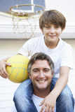 Father And Son Family Playing Basketball Outside Garage Stock Photo