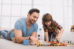 Father and son family time together at home. Playing toy cars Royalty Free Stock Images