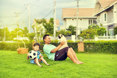 Father and son. Playing with dog in garden Royalty Free Stock Photos