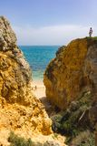 Father and son. Standing on top of a rock on a yellow beach in the Algarve, Portugal stock image