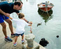 Father and son feed sea lion at a fishing dock Stock Photo