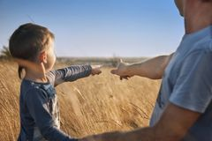 Father and son in the field at sunset, point fingers at the horizon, look afar, family, emotions, toned photo, effect. Father and son in the field at sunset Stock Photos