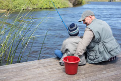Father and son fihsing at a lake. Father and son fishing at a lake in the countryside Royalty Free Stock Image