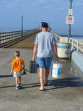 Father and son fishing. Father and son going fishing on pier Royalty Free Stock Photo