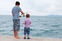 Father and son fishing. Back view of father and son fishing on summer day Royalty Free Stock Photo