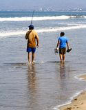 Father and son fishing. Father and son walking along a beach, carrying a fishing pole Stock Photography