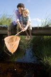 Father and son (6-8) fishing above stream on small wooden footbridge, boy holding fishing net, smiling, portrait Royalty Free Stock Images