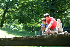 Father and son fishing from the birdge Stock Photos