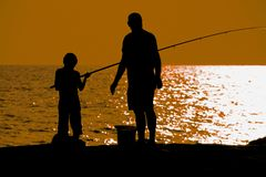 Father and son fishing. At dusk, silhouette, Cilento, Southern Italy Stock Photos