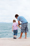 Father and son fishing from jetty. Vertical photo of father and son fishing from wooden jetty Stock Photography