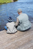 Father and son fishing at a lake. In the countryside Royalty Free Stock Photo
