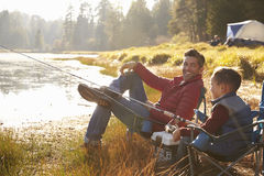 Father and son fishing by a lake, dad looks to camera Royalty Free Stock Photography