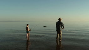 Father and son fishing on the lake. Fisherman on the lake in a cowboy hat stock footage