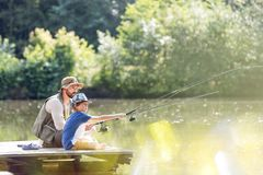 Father and son fishing in lake while sitting on pier royalty free stock photo