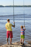 Father and son fishing. Father and son lake fishing together. They're using telescopic fishing rods, fishing line, floats, and baited fishing hooks. Man has Royalty Free Stock Photo