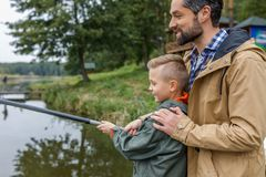 Father and son fishing on lake. Father and son fishing together with rod on lake Royalty Free Stock Image