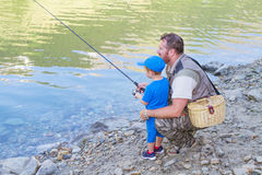 Father and son fishing in a mountain lake. A father and son fishing in a mountain lake Stock Image