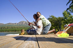 Father and son fishing off dock royalty free stock image