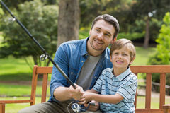 Father and son fishing on park bench Royalty Free Stock Photos