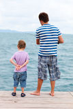 Father and son fishing from pier. Back view of father and son fishing from pier Royalty Free Stock Photography