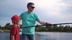 Father and son fishing on pier stock footage