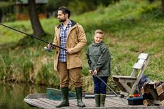 Father and son fishing on pier. Father and son fishing together with rods on wooden pier at lake Stock Photo