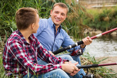 Father and son fishing on river. Glad father and his teenager son fishing together from water side at river Stock Photo