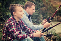 Father and son fishing on river. Glad father and his teenager son fishing together from water side on a river. Focus on child Royalty Free Stock Photography
