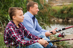 Father and son fishing on river. Glad father and his teenager son fishing together from water side at a river. Focus on child Royalty Free Stock Photo