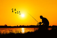 Father and son fishing in the river. Sunset backgrond Stock Photos