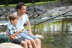 Father and son fishing in river stock images