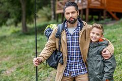 Father and son with fishing rod. And backpack at lake Stock Photos
